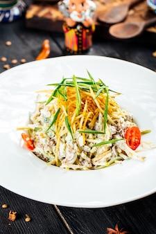 Close-up op de salade van rundvleesreepjes met groenten en spaanders op de zwarte houten lijst