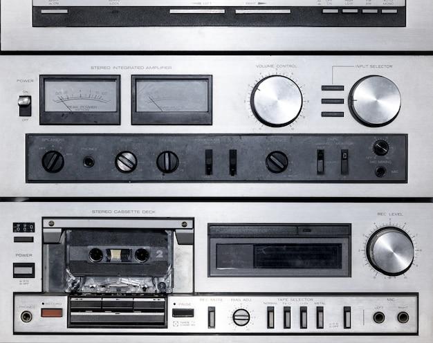 Close-up op de wijzerplaten en bedieningselementen van een vintage stereomuziekspeler met het cassettedeck voor oude audiocassettes
