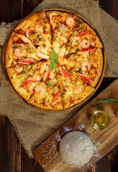 Close-up op deeg, olijfolie, poeder en deegroller voor het maken van zelfgemaakte zeevruchtenpizza met garnalen, krabsticks, paprika's op zak en houten tafel. voedselconcept.