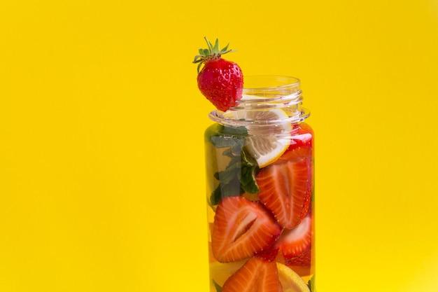 Close-up op doordrenkt of detoxwater met aardbei en citroen in de fles