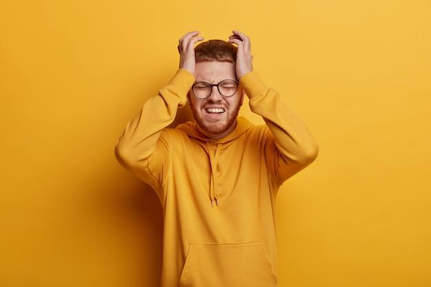 Close-up op een bebaarde jonge man met een bril geïsoleerd