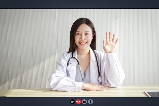 Close-up op een computerscherm, een mooie aziatische vrouwelijke arts behandelt een patiënt via online videogesprek