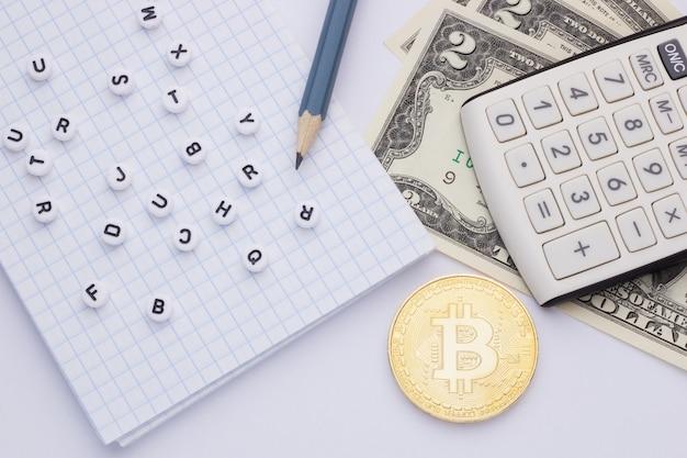 Close-up, op een witte achtergrondcalculator, geld (bitcoin) en blocnote met brieven