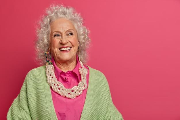 Close-up op elegante oudere vrouw, gekleed in stijlvolle kleding geïsoleerd