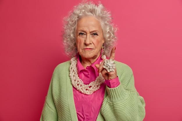 Close-up op elegante oudere vrouw, gekleed in stijlvolle kleding geïsoleerd Gratis Foto