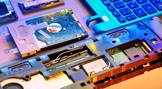 Close-up op elektronisch moederbord, neonlicht, hardware reparatiewerkplaats. wazig panoramisch beeld met geopende laptop circuits, close-up op elektronica. getinte achtergrond getint in oranje, paars en blauw.