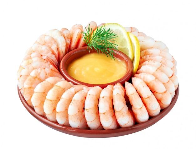 Close-up op garnalenring met zeevruchten sause, citroen en dille op wit wordt geïsoleerd dat