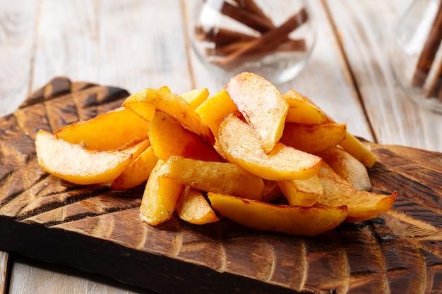 Close-up op gebakken aardappelpartjes op het houten bord