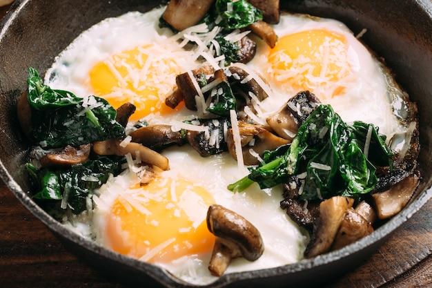 Close-up op gebakken eieren met champignons en spinazie in gietijzeren pan