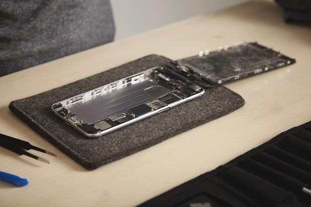 Close-up op gedemonteerde verdronken telefoon met verwijderde batterij en losgemaakt scherm in professioneel reparatielaboratorium