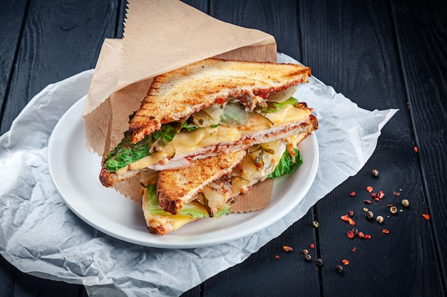 Close-up op gegrilde sandwich met kip en gesmolten kaas en sla