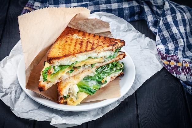 Close-up op gegrilde sandwich met verschillende soorten gesmolten kaas en sla