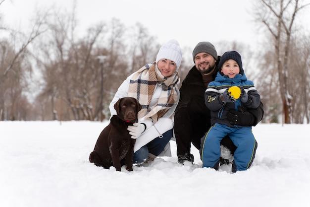 Close-up op gelukkige familie spelen in de sneeuw met hond