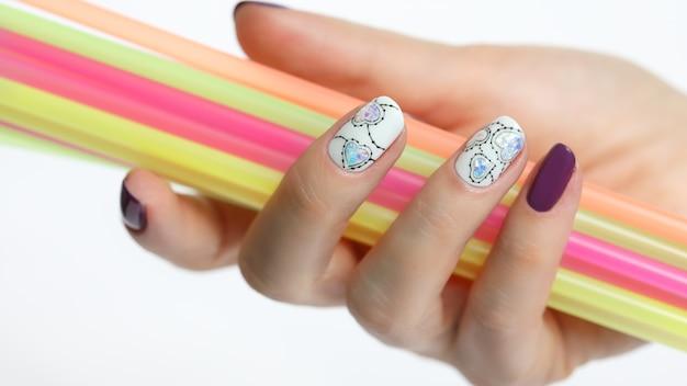Close-up op gemanicuurde hand met rietjes isoalted