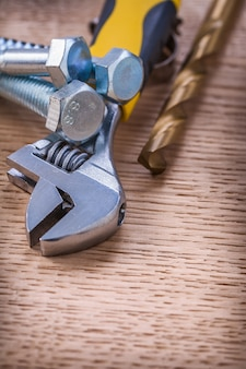 Close-up op gereedschap schroeven bouten moersleutel boor op houten plank
