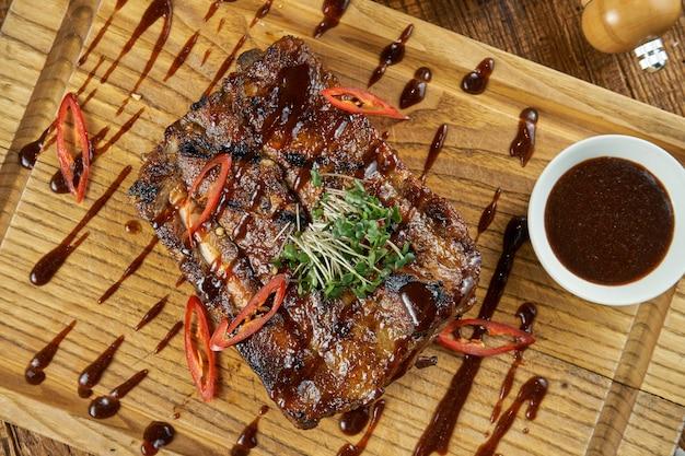 Close-up op geroosterde barbecue varkensribbetjes in zoetzure saus met salade op een lekker eten voor bier