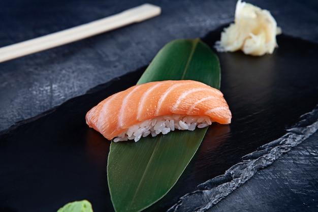 Close-up op geserveerd nigiri met zalm op donkere plaat op donkere ondergrond