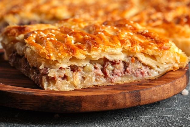 Close-up op gesneden taart met rundvlees en aardappelen vullen op de houten tafel