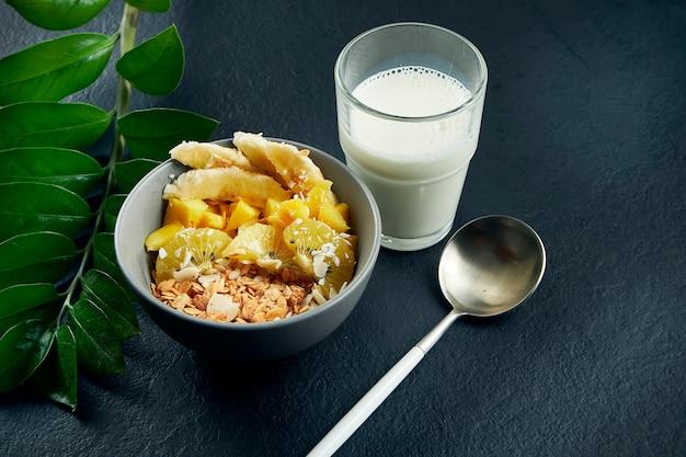 Close-up op gezond ontbijt: havermout met kokos, mango, bananen en gele kiwi in een blauwe kom geserveerd met melk op een zwarte tafel.