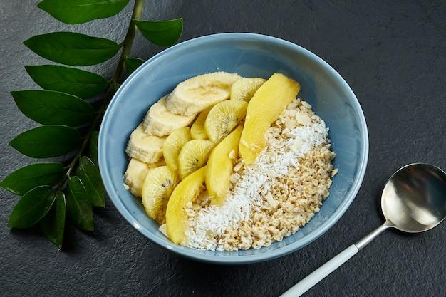 Close-up op gezond ontbijt: havermout met kokos, mango, bananen en gele kiwi in een blauwe kom op een zwarte ondergrond