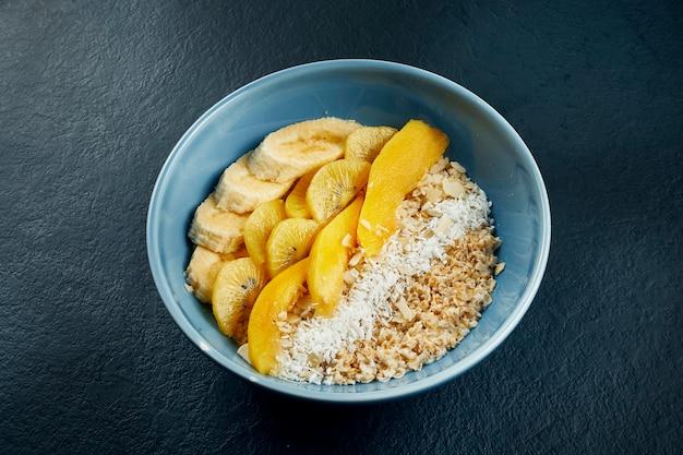 Close-up op gezond ontbijt: havermout met kokos, mango, bananen en gele kiwi in een blauwe kom op een zwarte tafel.