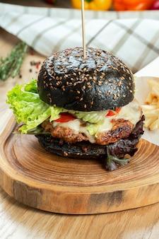 Close-up op hamburger met een zwart broodje met kotelet, kaas, tomaat en sla geserveerd met frietjes. houten muur. selectieve aandacht.