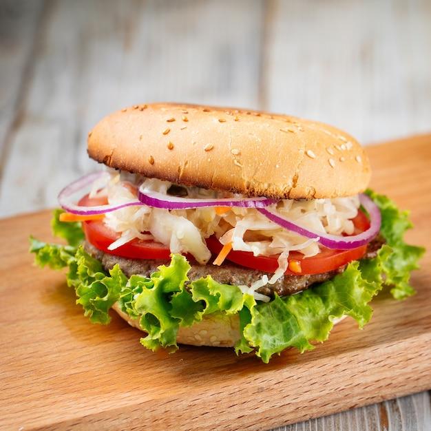 Close-up op hamburger met zuurkool en sla op het houten bord