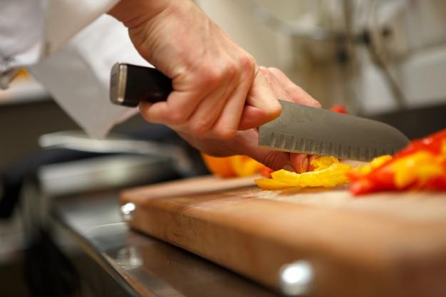 Close-up op handen die gele peper snijden