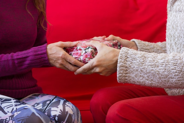 Close-up op handen die van vrouw kerstmis op rode laag geven