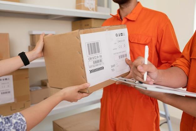 Close-up op handen leveringsdozen overhandigen aan koerier