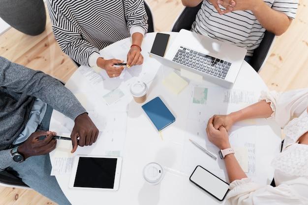 Close-up op handen van jonge collega's in een vergadering