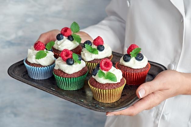 Close-up op handen van vrouwelijke chef-kok die een dienblad van verfraaide chocolade cupcakes houden