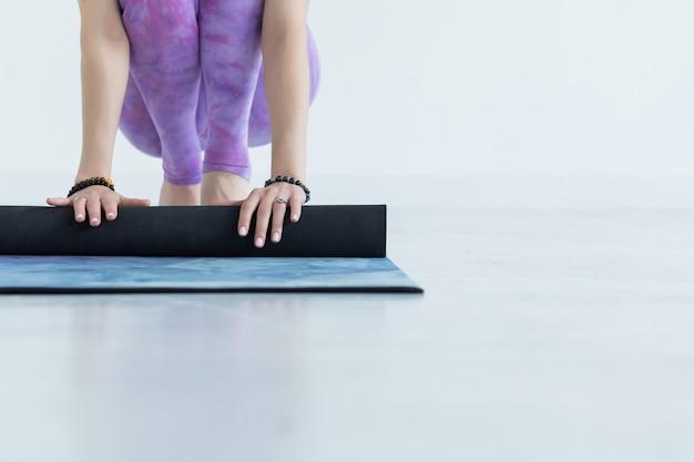 Close-up op handen yogavrouw die haar blauwe mat na een yoga rollen