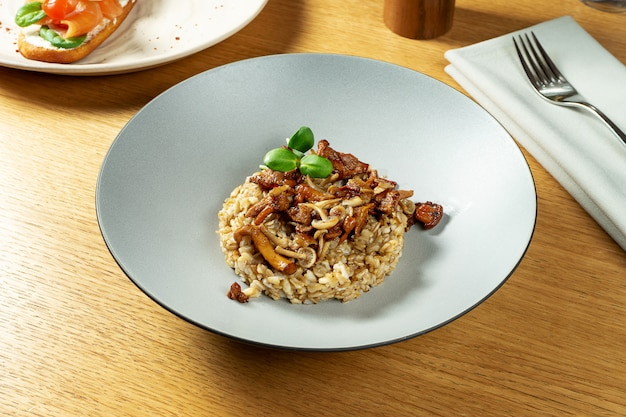 Close-up op heerlijk gekookt volkoren havermout met kleine bospaddestoelen. lekker vegetarisch eten. gezonde en evenwichtige maaltijd voor het ontbijt.