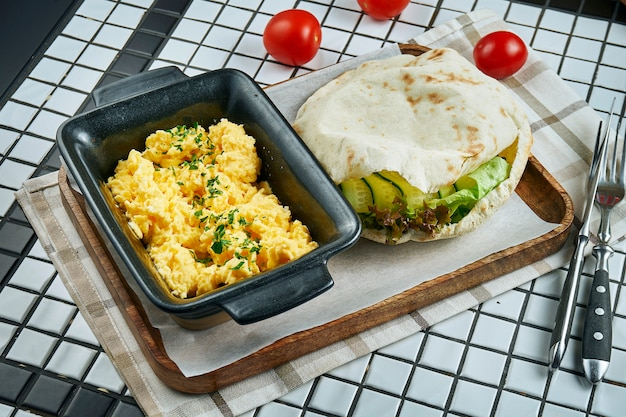 Close-up op heerlijk ontbijt: roerei met groenen met focaccia broodje geserveerd op perkament op witte tafel.