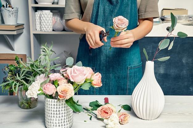 Close-up op het creatieve bloemistwerk. het wijfje die een boeket met bloemen schikken gebruikt bloemisthulpmiddelen die zich door werkplaats in winkel bevinden. bloemen bezorgen. kopieer ruimte. werkplek en professioneel concept