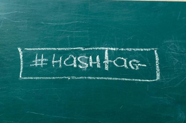 Close-up op het witte krijt van het hashtagsymbool op een groene ruimte van het bordexemplaar