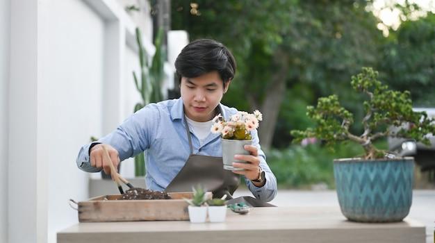 Close-up op jonge man thuis het planten van bloemen in een pot