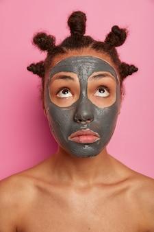 Close-up op jonge mooie vrouw met gezichtsmasker boven geconcentreerd, draagt een gezichtsmasker van klei voor het verminderen van acnes, staat naakt, geeft om lichaam, geïsoleerd op roze achtergrond, heeft veel gekamde broodjes op het hoofd