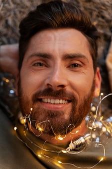 Close-up op jonge volwassene die geniet van kerstverlichting