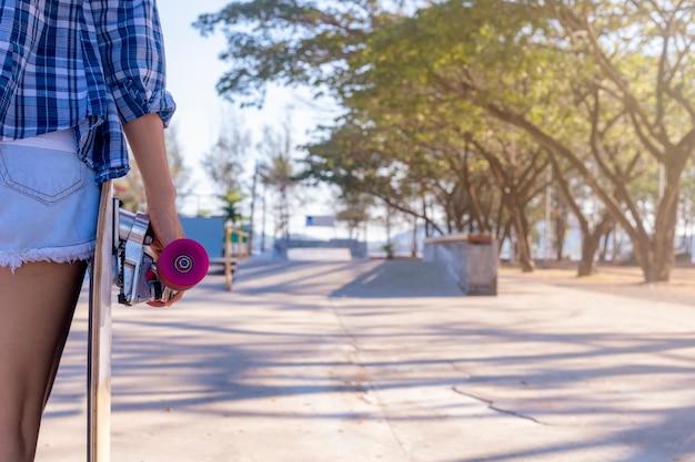 Close-up op jonge vrouw hand met een skateboard op openbare skate ramp park.