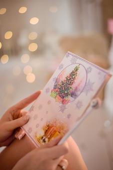 Close-up op kerstmisprentbriefkaar in vrouwenhanden