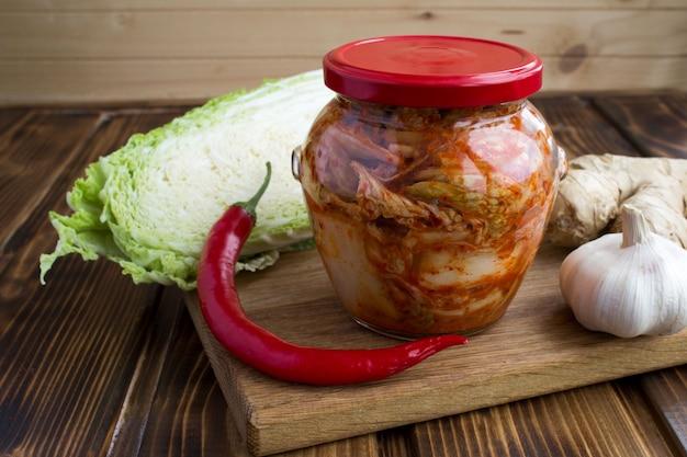 Close-up op kimchi in de glazen pot en ingrediënten op de snijplank