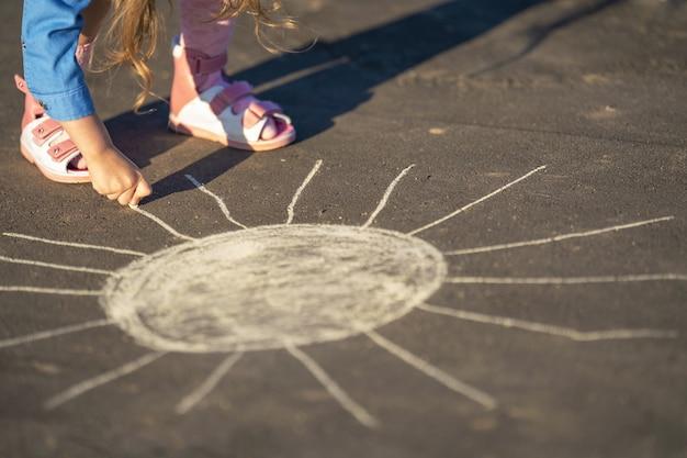 Close-up op kind tekenen met gekleurd krijt op asfalt