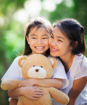 Close-up op klein aziatisch meisje knuffelen een teddybeer in park met haar moeder