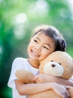 Close-up op klein aziatisch meisje knuffelen een teddybeer in park