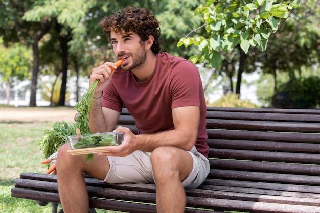 Close-up op knappe man eten in park