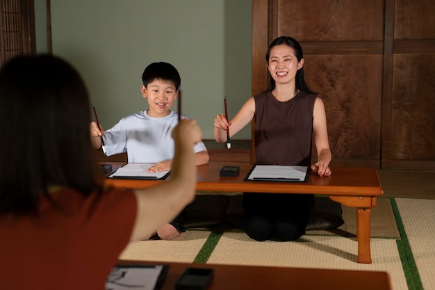 Close-up op leerlingen die japanse kalligrafie doen, genaamd shodo