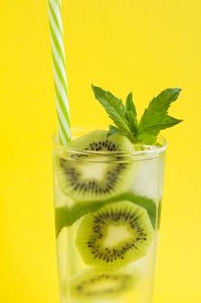Close-up op limonade met kiwi, ijs en munt op de gele achtergrond