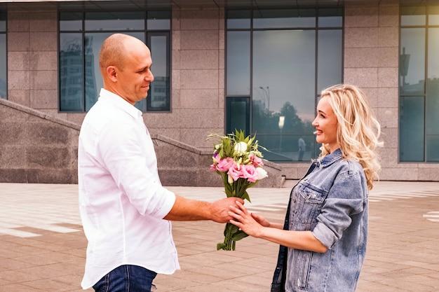 Close-up op man bloemen geven aan een vrouw